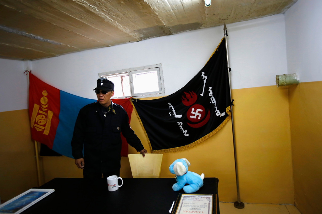 Description of . Ariunbold, a leader of the Mongolian neo-Nazi group Tsagaan Khass, arrives at the group's headquarters in Ulan Bator June 24, 2013. The group has rebranded itself as an environmentalist organisation fighting pollution by foreign-owned mines, seeking legitimacy as it sends Swastika-wearing members to check mining permits. Over the past years, ultra-nationalist groups have expanded in the country and among those garnering attention is Tsagaan Khass, which has recently shifted its focus from activities such as attacks on women it accuses of consorting with foreign men to environmental issues, with the stated goal of protecting Mongolia from foreign mining interests. This ultra-nationalist group was founded in the 1990s and currently has 100-plus members. Picture taken June 24, 2013.   REUTERS/Carlos Barria