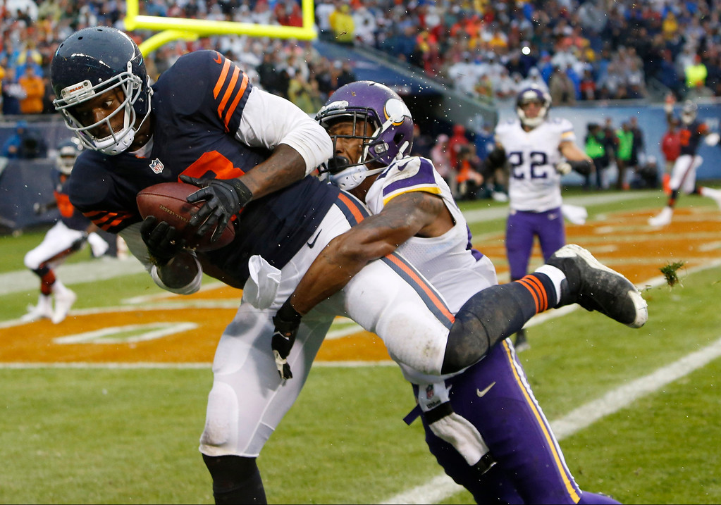 Description of . Chicago Bears tight end Martellus Bennett, left, catches the game-winning touchdown reception late in the second half of an NFL football game on Sunday against the Minnesota Vikings, Sunday, Sept. 15, 2013, in Chicago. Vikings cornerback Chris Cook defends. The Bears won 31-30.  (AP Photo/Charles Rex Arbogast)