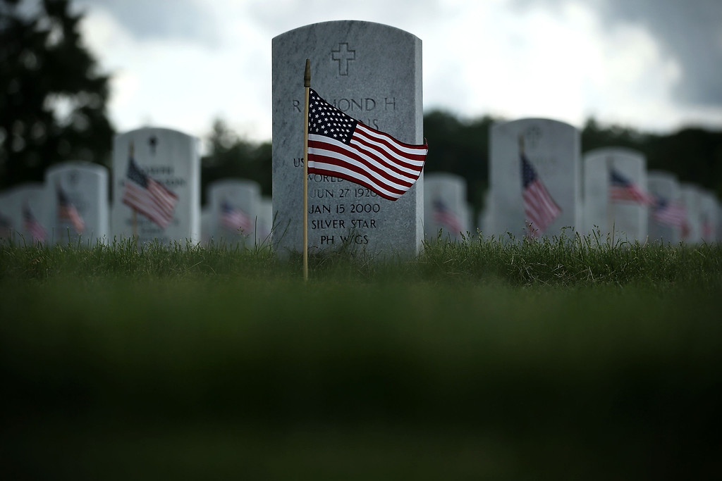 Description of . Small American flags are seen in front of graves during a