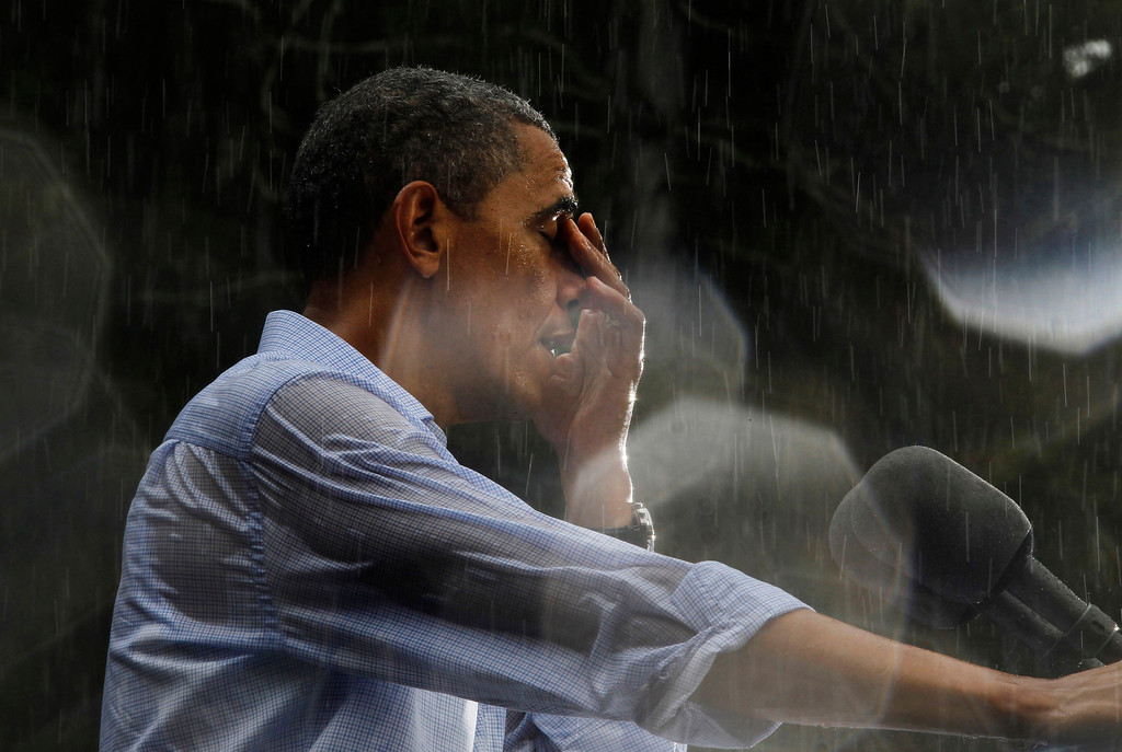 Description of . U.S. President Barack Obama wipes water off his face during a rain shower at a campaign rally in Glen Allen, Virginia, July 14, 2012. Obama travelled to Virginia on Saturday for campaign events. Rain drops on the lens created the highlights in the image. REUTERS/Jason Reed