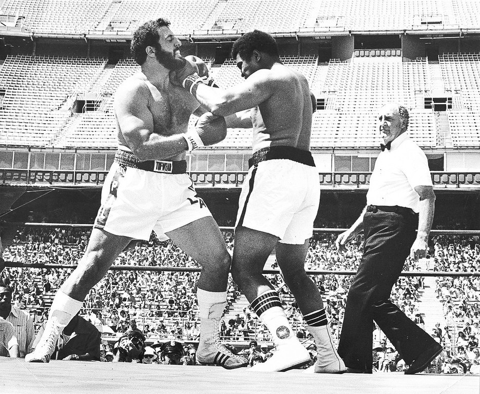 Description of . The Broncos Lyle Alzado, left, took on the former heavyweight champion Muhammad Ali at Mile High Stadium in July 1979. 11,128 people showed up at Mile High. The match lasted eight rounds. Alzado and some friends promoted the fight. He had even taken out a second mortgage on his house to guarantee that the event would go off as scheduled. Ticket sales generated slightly more than $200,000, considerably less than Ali's appearance fee of $250,000.    Historical Collection