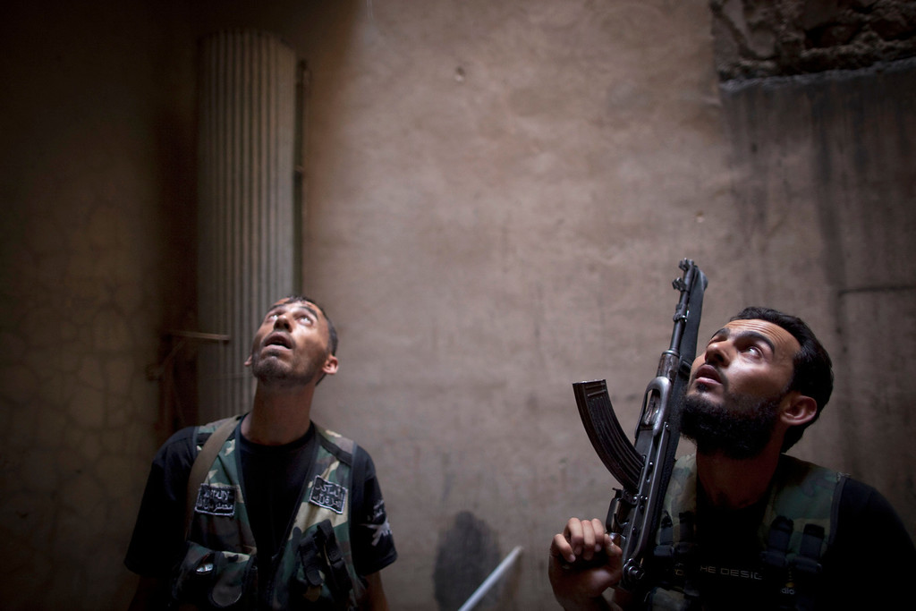 Description of . Rebel fighters look up listening as they take positions during clashes with pro-government forces in the Salaheddine district of the northern Syrian city of Aleppo, on July 9, 2013. JM LOPEZ/AFP/Getty Images