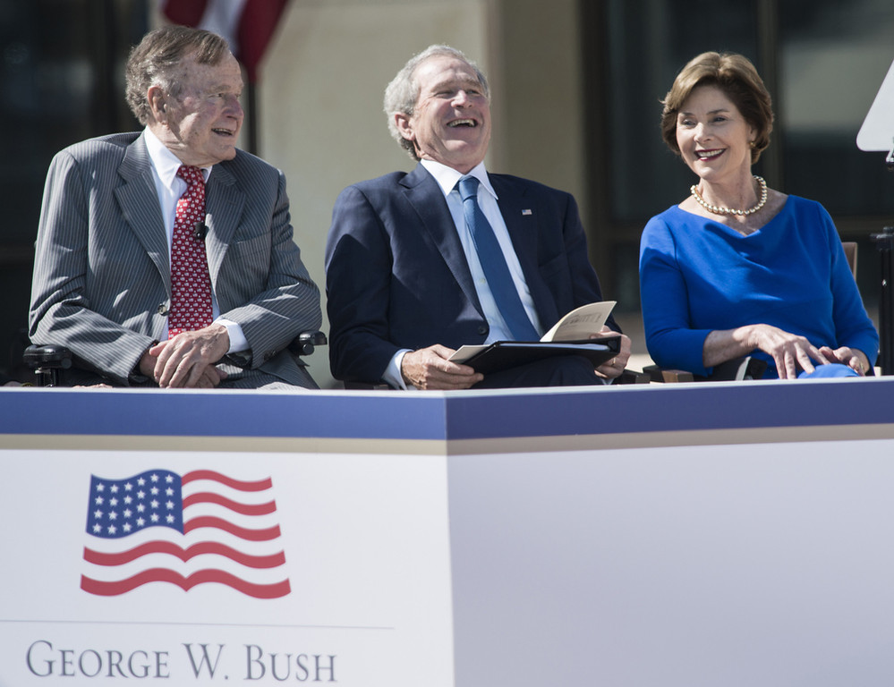 Description of . Former US President George H. W. Bush (L), former US President George W. Bush and Laura Bush listen during a dedication ceremony at the George W. Bush Library and Museum on the grounds of Southern Methodist University April 25, 2013 in Dallas, Texas. The Bush library is dedicated to chronicling the presidency of the United State's 43rd President, George W. Bush.  BRENDAN SMIALOWSKI/AFP/Getty Images