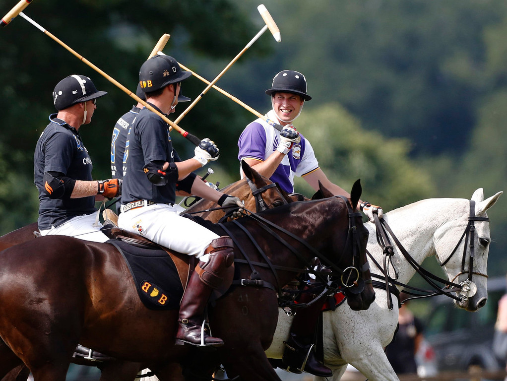 Description of . Britain\'s Prince William (R) rides onto the pitch with the opposing team at the start of the Jerudong Trophy polo match at Cirencester Park Polo Club near Cirencester in central England July 14, 2013. REUTERS/Luke MacGregor