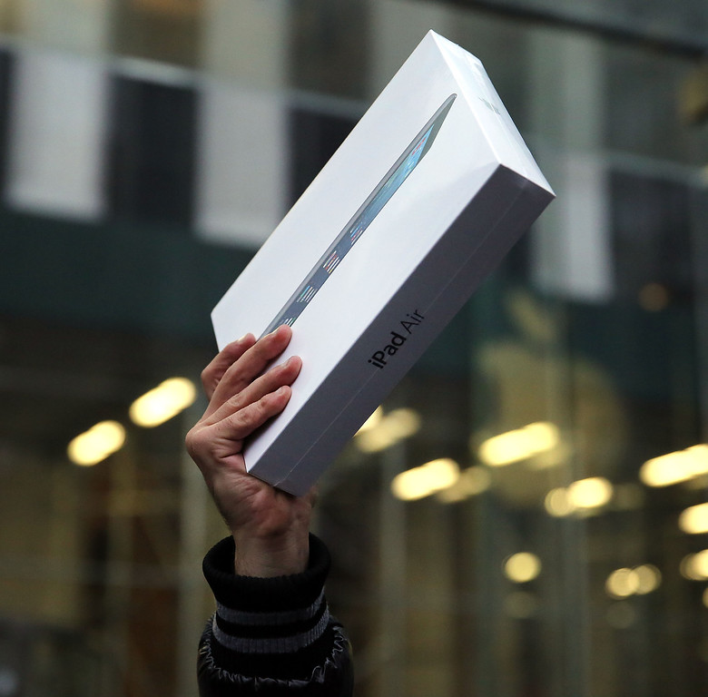 Description of . The first customer in line, Rami Shamis, holds up his new iPad Air at the Apple Store on November 1, 2013 in New York City.   (Photo by Spencer Platt/Getty Images)