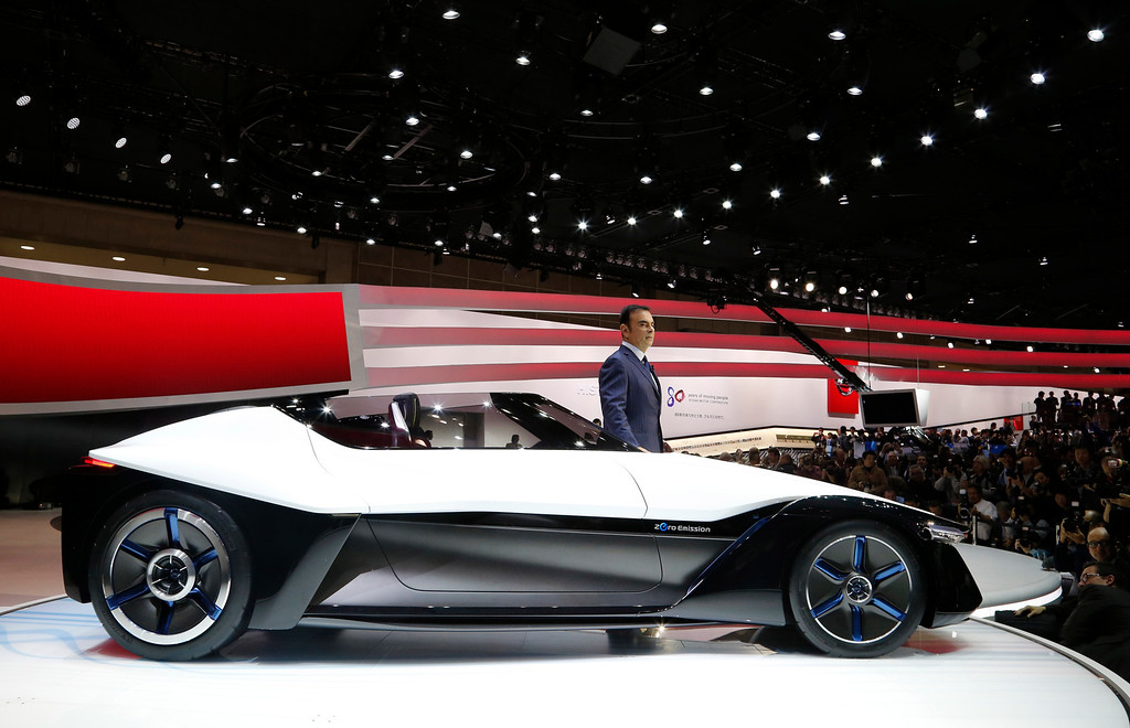 Description of . Nissan Motor Co. President and CEO Carlos Ghosn poses with a Nissan BladeGlider concept car at the media preview for the Tokyo Motor Show at Tokyo Big Sight in Tokyo, Wednesday, Nov. 20, 2013.  (AP Photo/Shuji Kajiyama)