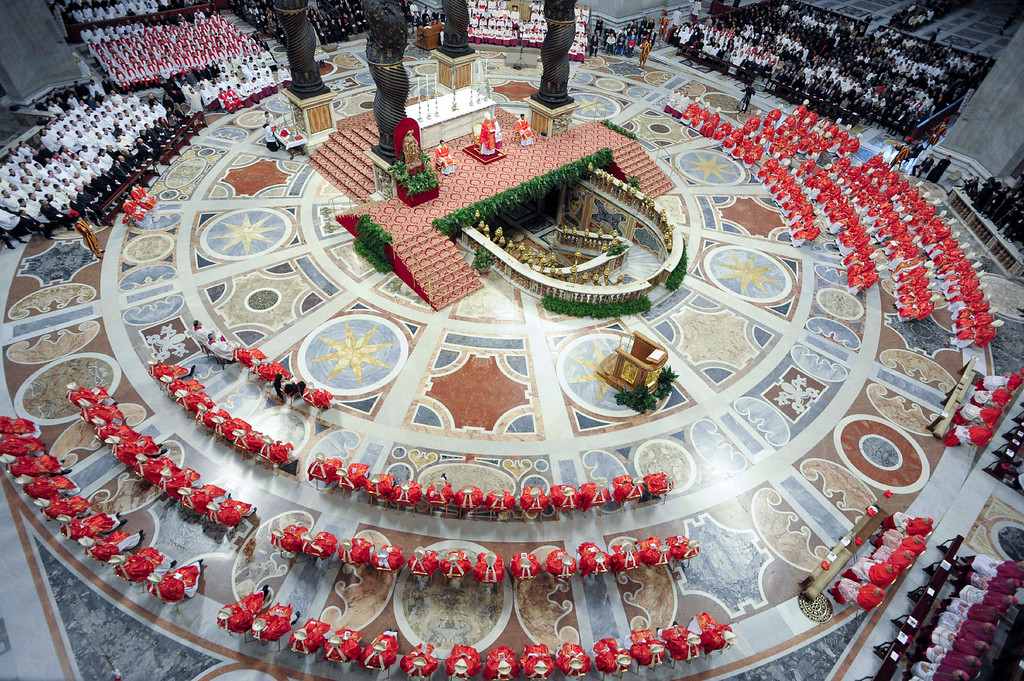 Description of . In this photo provided by the Vatican newspaper L\'Osservatore Romano, cardinals, in red, attend a Mass for the election of a new pope celebrated by Cardinal Angelo Sodano, figure at the center of the stage beneath the Bernini baldachin, inside St. Peter\'s Basilica, at the Vatican, Tuesday, March 12, 2013. Cardinals enter the Sistine Chapel on Tuesday to elect the next pope amid more upheaval and uncertainty than the Catholic Church has seen in decades: There\'s no front-runner, no indication how long voting will last and no sense that a single man has what it takes to fix the many problems. (AP Photo/L\'Osservatore Romano, ho)