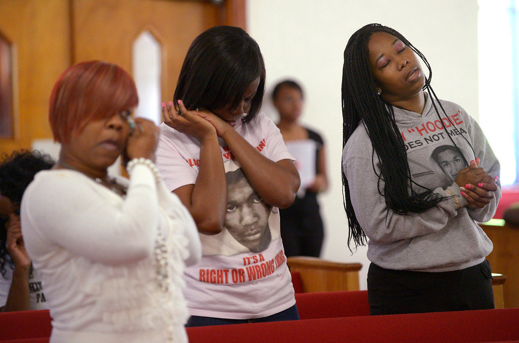 Description of . Tammy Haynes, left, Whitney Tillman, center, and Crystal Haynes react during a sermon at a youth service at the St. Paul Missionary Baptist Church in Sanford, Fla., Sunday, July 14, 2013.  Many in the congregation wore shirts in support of Trayvon Martin following the acquittal of  George Zimmerman, who had been charged in the 2012 shooting death of  Martin.  (AP Photo/Phelan M. Ebenhack)