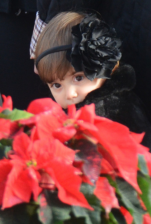 . Staff photos by Tom Kelly IV A young girl dressed all in black, looks at a poinsetta, which is part of a small memorial outside of the church.  Funerals for two, six year old students from the Sandy Hook Elementary School in Newtown, CT took part Tuesday December 18, 2012.  Mourners paid their respects at the Saint Rose of Lima Church.