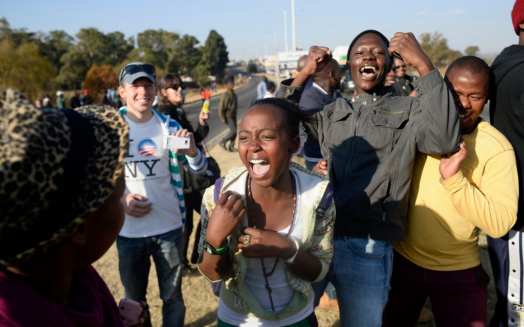 Description of . Bystanders cheer after catching a brief glimpse of U.S. President Barack Obama as he arrives at the University of Johannesburg in Soweto, June 29, 2013.  REUTERS/Dylan Martinez