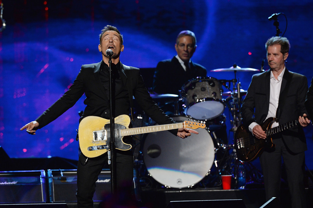 Description of . (L-R) Bruce Springsteen and inductees Max Weinberg and Garry Tallent of the E Street Band perform onstage at the 29th Annual Rock And Roll Hall Of Fame Induction Ceremony at Barclays Center of Brooklyn on April 10, 2014 in New York City.  (Photo by Larry Busacca/Getty Images)