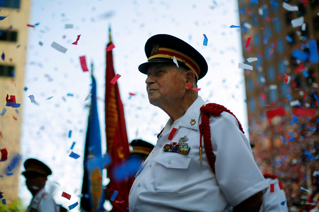 Description of . A member of the Ancient and Honorable Artillery Company stands amid confetti following a reading the United States Declaration of Independence, part  Fourth of July Independence Day celebrations, in Boston, Massachusetts July 4, 2013. People across the United States gathered on Thursday for parades, picnics and fireworks at Independence Day celebrations, held under unprecedented security following the Boston Marathon bombings. Spectators waving U.S. flags and wearing red, white and blue headed for public gatherings in Boston, New York, Washington, Atlanta and other cities under the close watch of police armed with hand-held chemical detectors, radiation scanners and camera surveillance, precautions sparked by the deadly April 15 bombings.     REUTERS/Brian Snyder