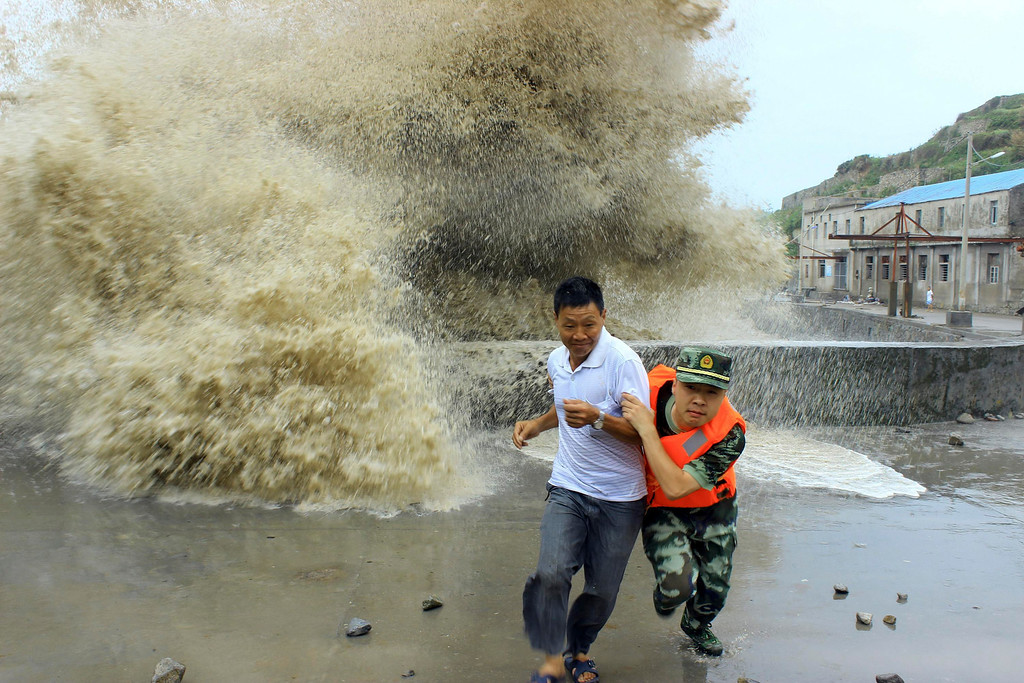 Description of . A frontier soldier helps a man move away from waves ahead of Typhoon Soulik in Wenzhou, Zhejiang province, July 13, 2013. China braced on Friday for the impact of Typhoon Soulik as the toll of dead and missing from torrential rain across a broad swathe of China climbed beyond 200. REUTERS/China Daily