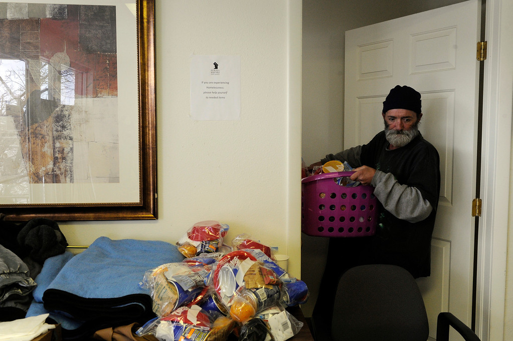 Description of . AURORA, CO - NOVEMBER 21: Virgil Barry brings out a laundry basket full of packaged food items during an Aurora Warms the Night Cold Weather Shelter Program on November 21, 2013, in Aurora, Colorado. Barry used to receive assistance from the shelter program himself, but when he attained housing earlier this month, he decided to return to Aurora Warms the Night (AWTN) to volunteer. AWTN provides assistance to the homeless with a number of initiatives, including the Cold Weather Shelter Program which gives clients motel vouchers, food, clothing and hygiene kits on nights expected to be 20 degrees or colder. (Photo by Anya Semenoff/YourHub)