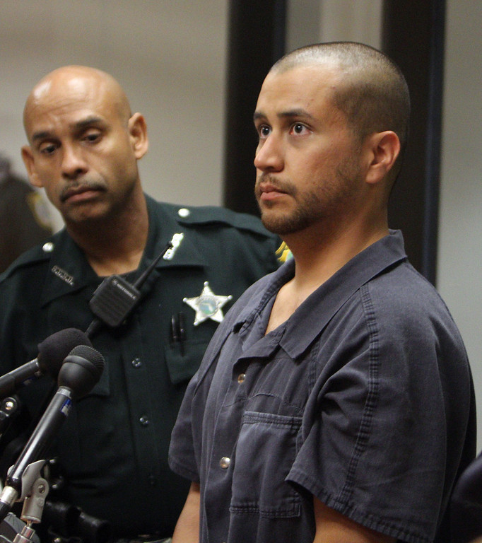 Description of . In this April 12, 2012 file photo, George Zimmerman, right, stands with a Seminole County Deputy during a court hearing in Sanford, Fla.  Zimmerman was charged with second-degree murder in the shooting death of the 17-year-old Trayvon Martin. (AP Photo/Gary W. Green, Orlando Sentinel, Pool, File)