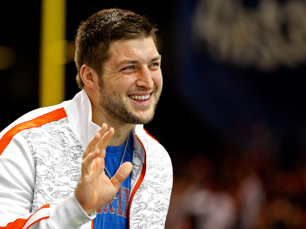 Description of . Former Florida Gators quarterback Tim Tebow waves as he stands on the sidelines before the Gators play against the Louisville Cardinals in the 2013 Allstate Sugar Bowl NCAA football game in New Orleans, Louisiana January 2, 2013. Tebow now plays for the NFL's New York Jets.  REUTERS/Jonathan Bachman (UNITED STATES  - Tags: SPORT FOOTBALL)
