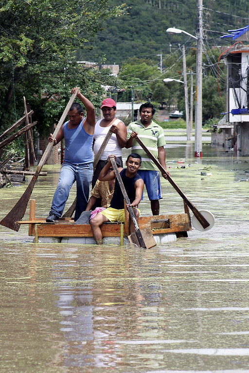 Description of . Residents attemp to cross a flooded street using a makeshift raft in Chilpancingo, state of Guerrero, Mexico, on September 17, 2013. Mexican authorities scrambled Tuesday to launch an air lift to evacuate tens of thousands of tourists stranded amid floods in the resort of Acapulco following a pair of deadly storms. The official death toll rose to 47 after the tropical storms, Ingrid and Manuel, swarmed large swaths of the country during a three-day holiday weekend, sparking landslides and causing rivers to overflow in several states. EDUARDO GUERRERO/AFP/Getty Images