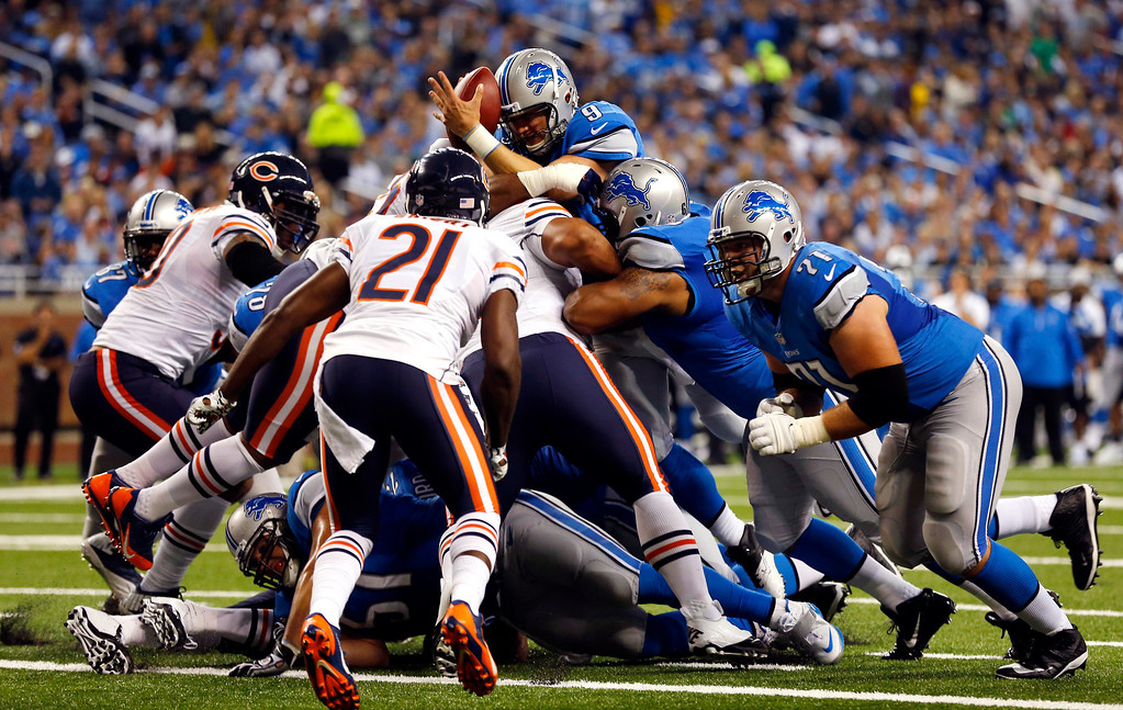 Description of . Detroit Lions quarterback Matthew Stafford (9) goes over the center for a touchdown but loses control of the ball during the second quarter of an NFL football game against the Chicago Bears at Ford Field in Detroit, Sunday, Sept. 29, 2013. (AP Photo/Paul Sancya)