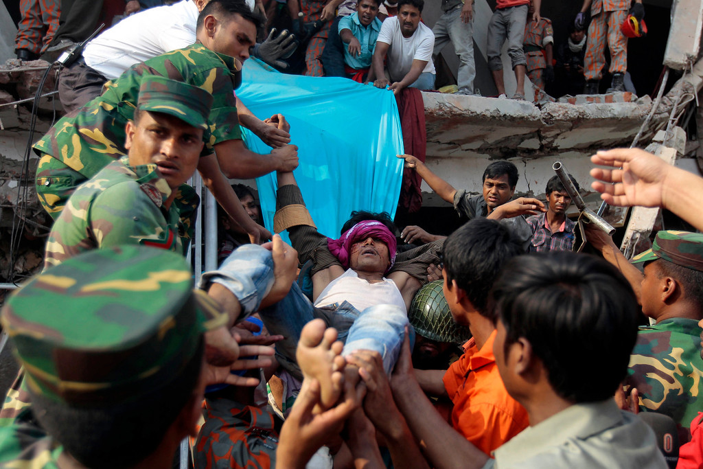 Description of . Rescuers carry a survivor out from the debris of a building that collapsed in Savar, near Dhaka, Bangladesh, Wednesday, April 24, 2013. (AP Photo/A.M.Ahad)