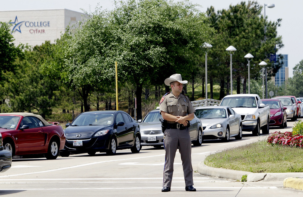 Description of . A Texas State Trooper stands at an entrance as vehicles leave from the Cy-Fair campus of Lone Star Community College in Cypress, Texas on Tuesday, April 9, 2013.   (AP Photo/Houston Chronicle, Melissa Phillip)