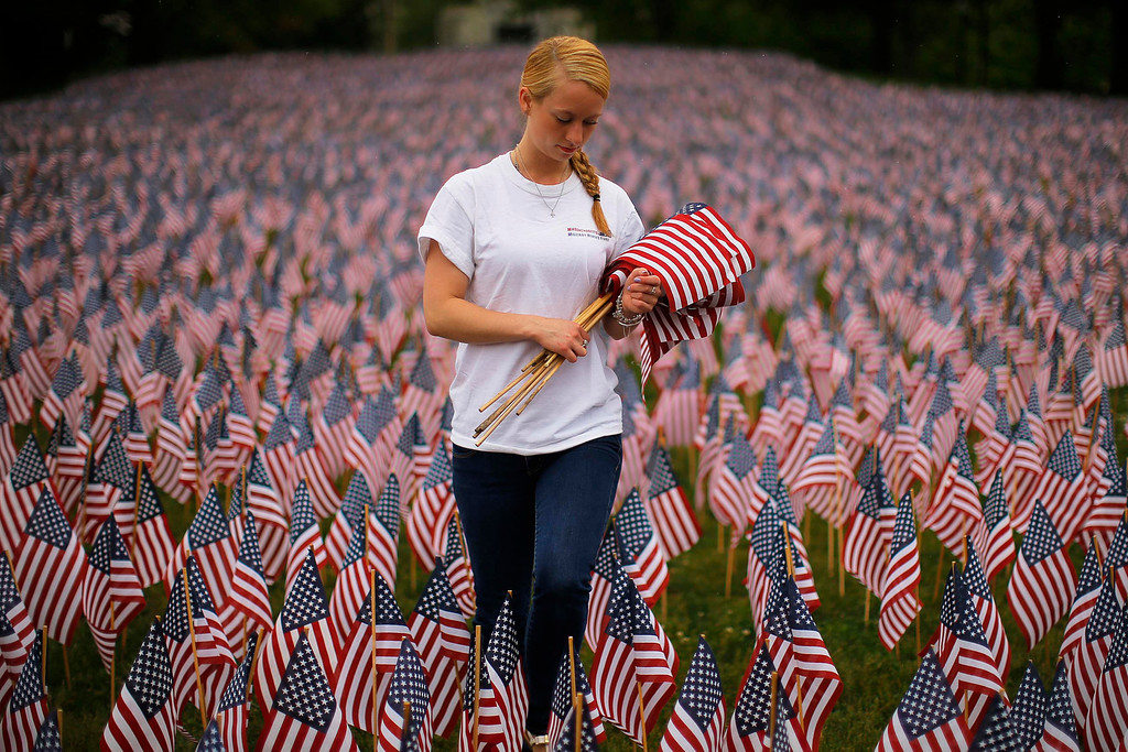 . Shannon Day, a volunteer with Massachusetts Military Heroes Fund, replaces broken flags at a Memorial Day display of United States flags on the Boston Common in Boston, Massachusetts May 23, 2013. According to the Massachusetts Military Heroes Fund, the flags are planted on the Common for fallen Massachusetts service members at the Memorial Day holiday, which will be celebrated May 27 in the U.S.   REUTERS/Brian Snyder
