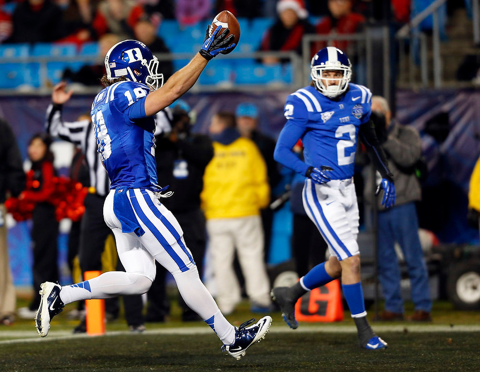 Description of . Duke's Brandon Connette (18) celebrates his touchdown run against Cincinnati as Conner Vernon (2) watches during the first half of the Belk Bowl NCAA college football game in Charlotte, N.C., Thursday, Dec. 27, 2012. (AP Photo/Chuck Burton)