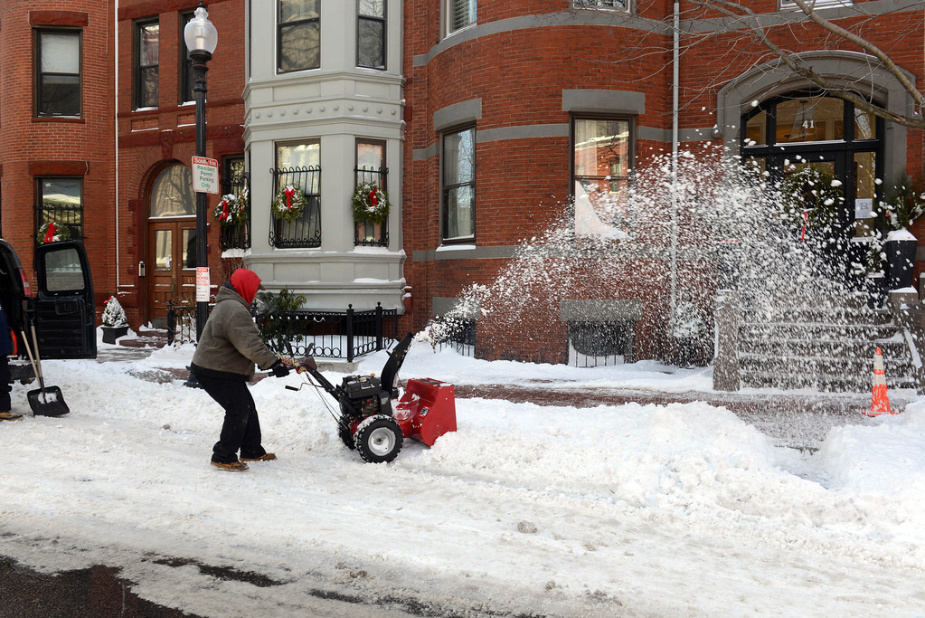 Description of . A man snow blows on East Concord Street in the South End after a two day winter storm January 4, 2014 in Boston, Massachusetts. The storm began mid day Thursday with heavy snows overnight into Friday bringing with it extreme cold. (Photo by Darren McCollester/Getty Images)