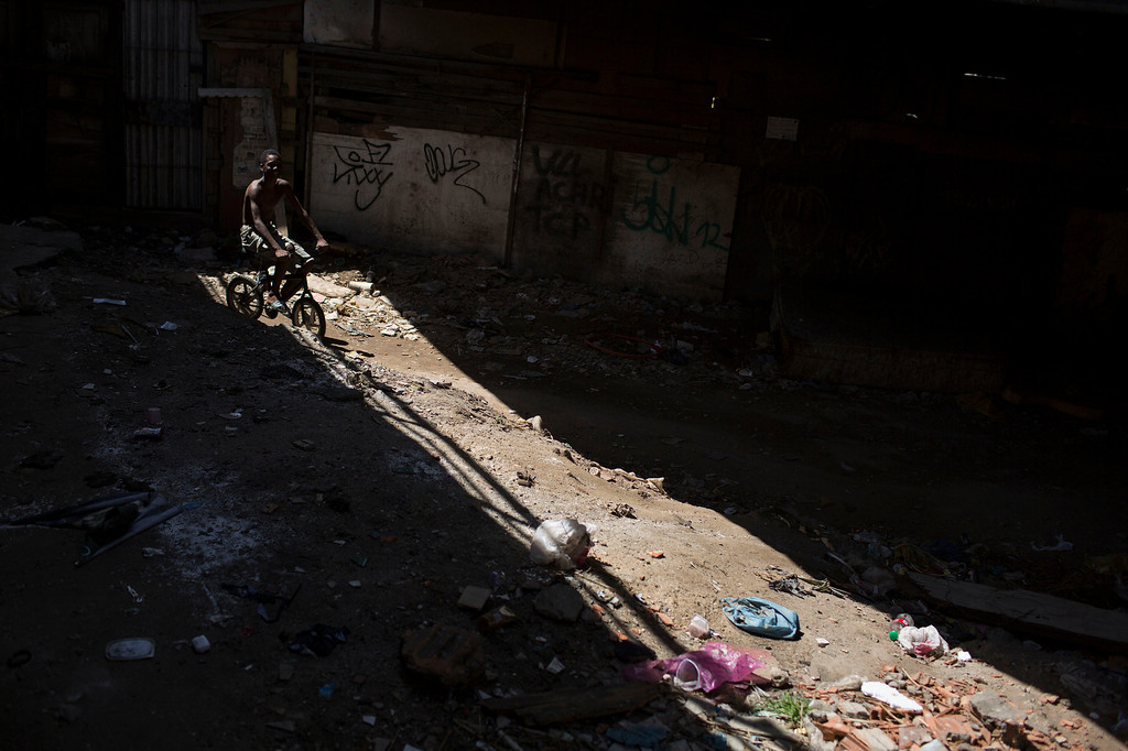 . A boy rides his bike in a poor area of the Mare slum complex in Rio de Janeiro, Brazil, Saturday, April 5, 2014. More than 2,000 Brazilian soldiers stormed into the slum complex Saturday with armored personnel carriers and helicopters in a bid to improve security two months before the start of the World Cup. (AP Photo/Felipe Dana)