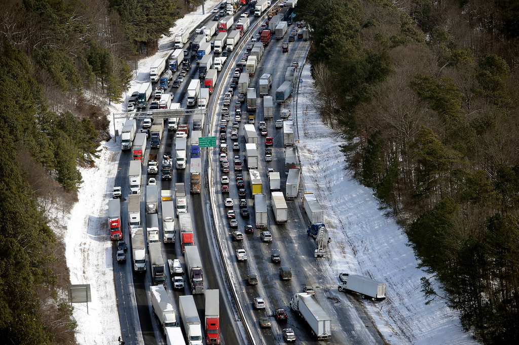 Description of . In this aerial photo, traffic is snarled along the I-285 perimeter north of the metro area after a winter snow storm, Wednesday, Jan. 29, 2014, in Atlanta.   (AP Photo/David Tulis)