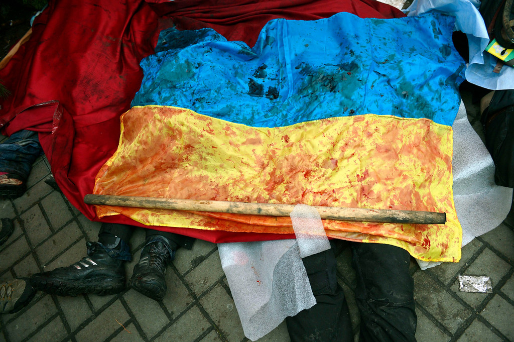 Description of . A bloody Ukranian flag covers the bodies of killed protesters in Kiev, Ukraine, 20 February 2014. More than 60 people have been killed in street fighting in Kiev on Thursday, the nationalist Svoboda opposition party says.  EPA/LASZLO BELICZAY