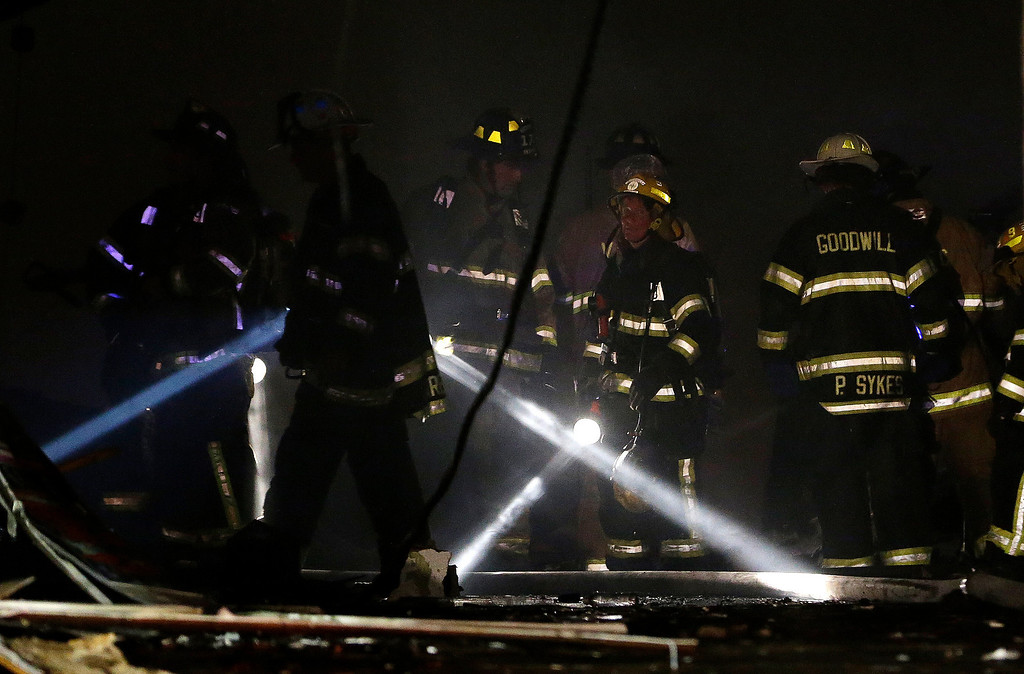 Description of . Firefighters use flashlights while checking an area where they fought off flames during a massive fire at the Seaside Park boardwalk, Thursday, Sept. 12, 2013, in Seaside Park, N.J. The fire, which apparently started in an ice cream shop and spread several blocks, hit the recently repaired boardwalk, which was damaged last year by Superstorm Sandy. There were no other early reports of any injuries. (AP Photo/Julio Cortez)