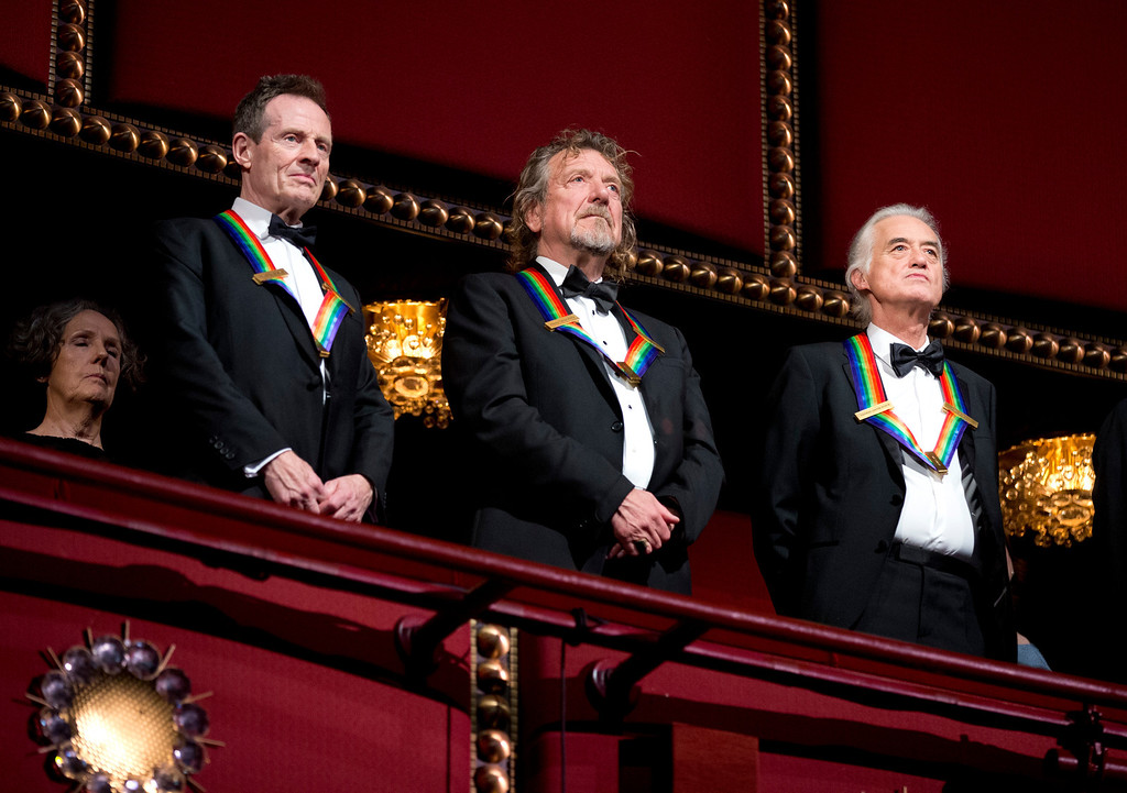 Description of . Rock band Led Zeppelin, from left, keyboardist/bassist John Paul Jones, singer Robert Plant, guitarist Jimmy Page, stand as the Star Spangled Banner is played during the Kennedy Center Honors Gala at the Kennedy Center in Washington, Sunday, Dec. 2, 2012. While Led Zeppelin is being honored as a band, surviving members Jones, Page, and Plant, each received the Kennedy Center Honors. (AP Photo/Manuel Balce Ceneta)