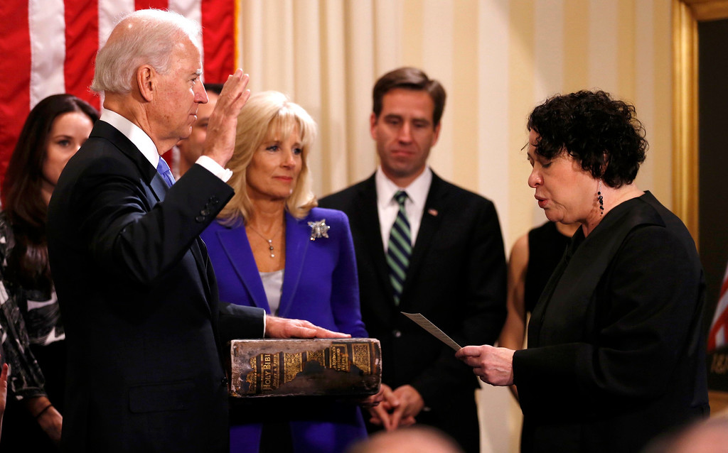 Description of . U.S. Vice President Joe Biden (L) takes the oath of office from Supreme Court Justice Sonia Sotomayor as his wife Jill Biden holds the family bible while family members look on at the U.S. Naval Observatory in Washington January 20, 2013.     REUTERS/Kevin Lamarque
