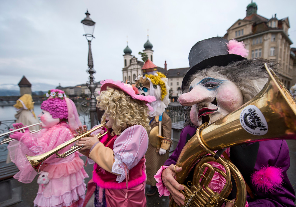 Description of . Members of a carnival band in costumes attend the opening of the Lucerne carnival in Lucerne, Switzerland, on the so-called dirty Thursday, Feb. 27, 2014. (AP Photo/Keystone, Sigi Tischler)