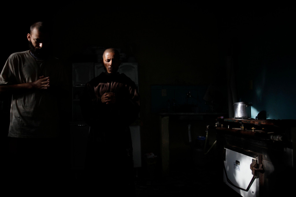 Description of . Jose Wellington Damasio (L) and Antonio, members of the Franciscan fraternity O Caminho, pray before breakfast in the kitchen of fraternity's house in the Campo Grande neighbourhood of Rio de Janeiro April 2, 2013. O Caminho (The Way) are a group of Franciscan monks and nuns who help the homeless on the streets of Rio de Janeiro. They consider the election of Pope Francis, the first pontiff to take the name of St Francis of Assisi, to be a confirmation of their beliefs in poverty and simplicity. In July, Pope Francis will visit Rio de Janeiro in his first international trip since assuming the papacy. Picture taken April 2, 2013. REUTERS/Ricardo Moraes