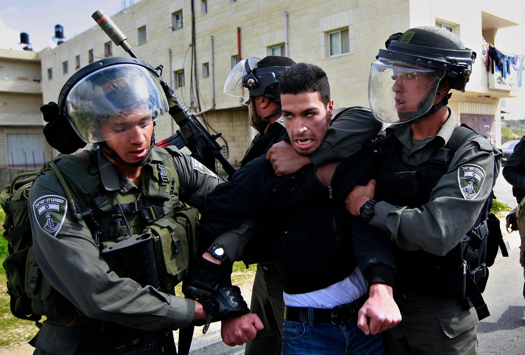 Description of . Isreali border policemen arrest a Palestinian man during a protest to support Palestinian prisoners, outside Ofer, an Israeli military prison near the West Bank city of Ramallah, Thursday, Feb. 28, 2013. (AP Photo/Majdi Mohammed)