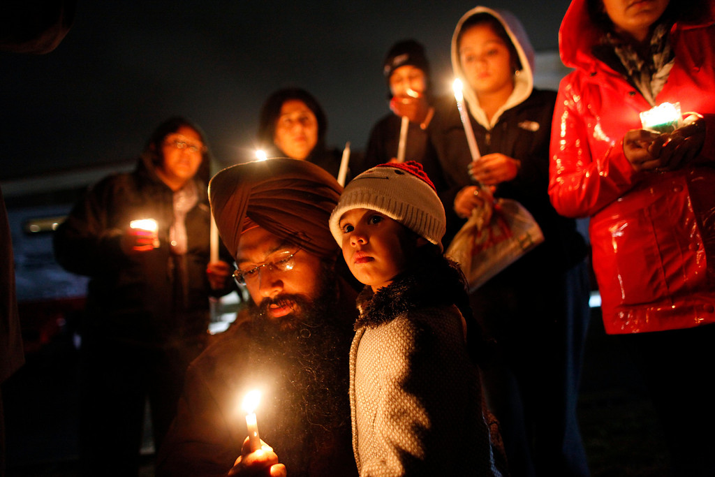 Description of . Eknoor Kaur, 3, stands with her father Guramril Singh during a candlelight vigil outside Newtown High School before an interfaith vigil with President Barack Obama, Sunday, Dec. 16, 2012, in Newtown, Conn.  A gunman walked into Sandy Hook Elementary School in Newtown Friday and opened fire, killing 26 people, including 20 children. (AP Photo/Jason DeCrow)