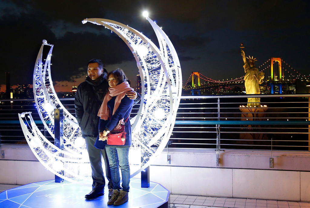 Description of . A couple poses in front of the Christmas illuminations for souvenir photos at Tokyo's Daiba bay area, Tuesday, Dec. 24, 2013. (AP Photo/Shizuo Kambayashi)