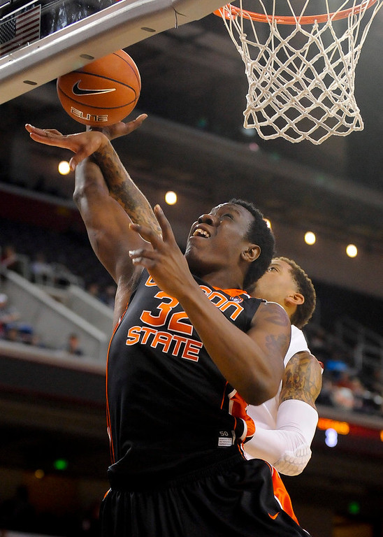 Description of . Oregon State forward Jarmal Reid (32) and Southern Cal guard J.T. Terrell, back right, fight for a rebound during the first half of an NCAA college basketball game, Saturday, Jan. 19, 2013, in Los Angeles. (AP Photo/Gus Ruelas)