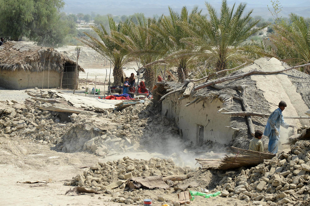 Description of . Pakistani earthquake survivors search through the debris of their collapsed houses in the devastated district of Awaran on September 25, 2013.  AFP PHOTO/Banaran KHAN/AFP/Getty Images