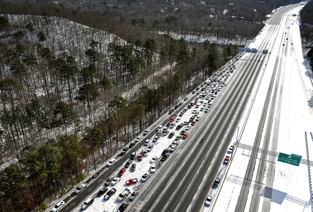 Description of . In this view looking south toward downtown Atlanta near the I-75 Chattahoochee River overpass, abandoned cars are piled up on the median of the ice-covered interstate after a winter snow storm slammed the city with over 2 inches of snow that turned highways into parking lots creating massive traffic jams lasting through Wednesday, Jan. 29, 2014, in Atlanta. While such amounts of accumulation barely quality as a storm in the north, it was enough to paralyze the Deep South. (AP Photo/David Tulis)