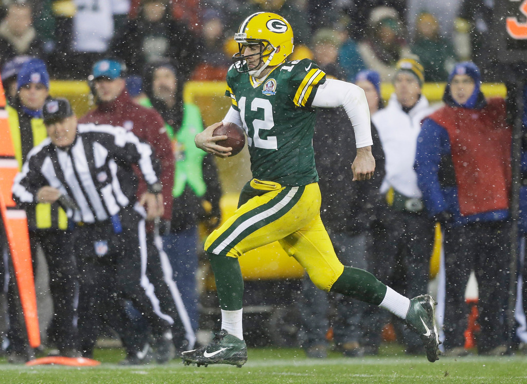 Description of . Green Bay Packers quarterback Aaron Rodgers breaks away for a 27-yard touchdown run during the second half of an NFL football game against the Detroit Lions Sunday, Dec. 9, 2012, in Green Bay, Wis. (AP Photo/Jeffrey Phelps)