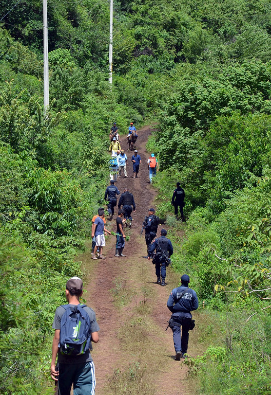 Description of . Federal police patrol a small country road after a slew of robbery reports of residents affected by Tropical Storm Manuel, who were trekking supplies back to their homes, near Tepechicotlan, Mexico, Thursday, Sept. 19, 2013. (AP Photo/Alejandrino Gonzalez)