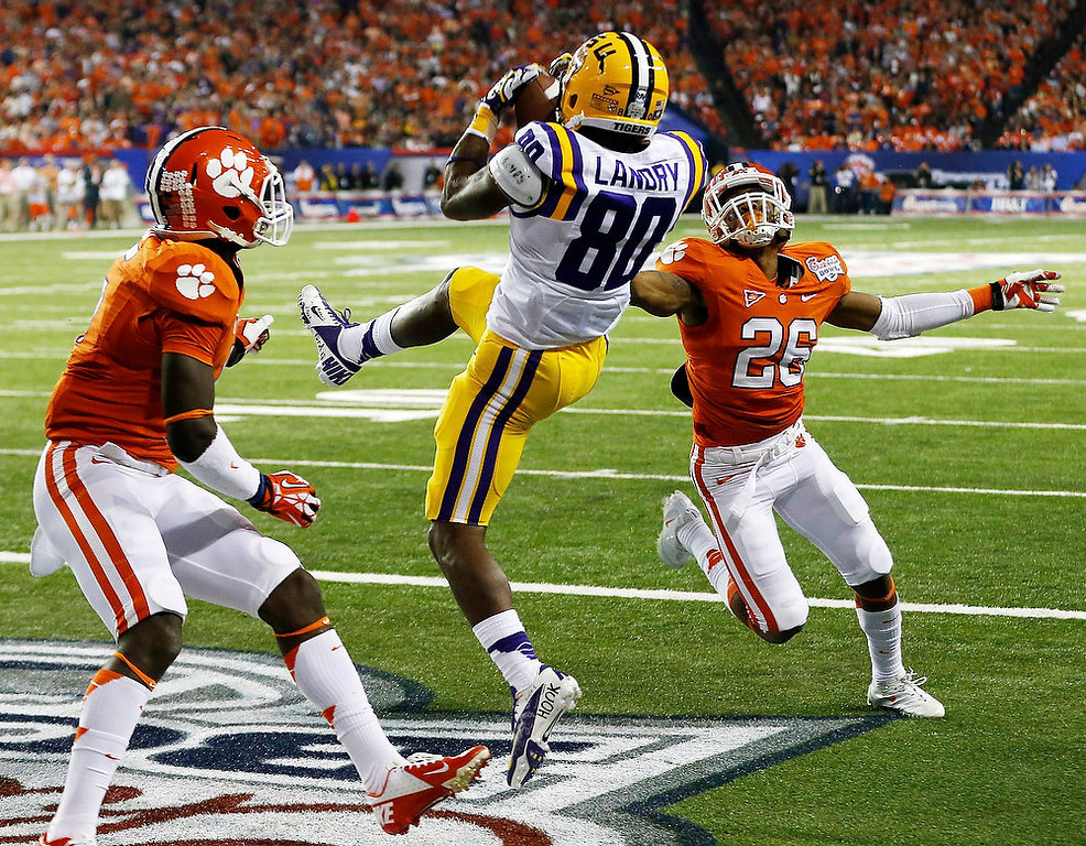 Description of . Clemson safety Jonathan Meeks, left, and defensive back Garry Peters (26) defend as LSU wide receiver Jarvis Landry (80) makes a touchdown catch during the first half of the Chick-fil-A Bowl NCAA college football game, Monday, Dec. 31, 2012, in Atlanta. (AP Photo/John Bazemore)