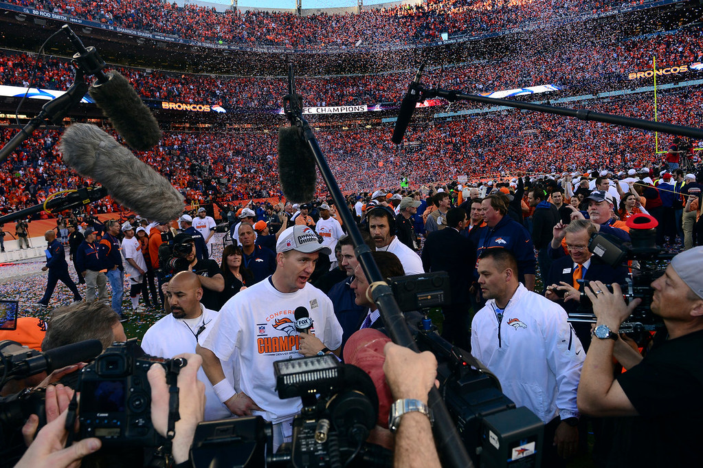 Description of . Denver Broncos quarterback Peyton Manning (18) is interviewed on the field after the Broncos won the AFC Championship game.  The Denver Broncos vs. The New England Patriots in an AFC Championship game  at Sports Authority Field at Mile High in Denver on January 19, 2014. (Photo by Helen Richardson/The Denver Post)
