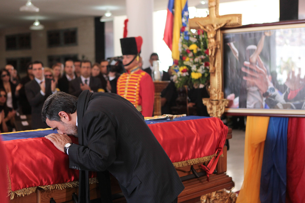 Description of . In this photo released by Miraflores Press Office, Iran's President Mahmoud Ahmadinejad kisses the flag-draped coffin of late Venezuela's President Hugo Chavez during the funeral ceremony at the military academy in Caracas, Venezuela, Friday, March 8, 2013. (AP Photo/Miraflores Press Office)