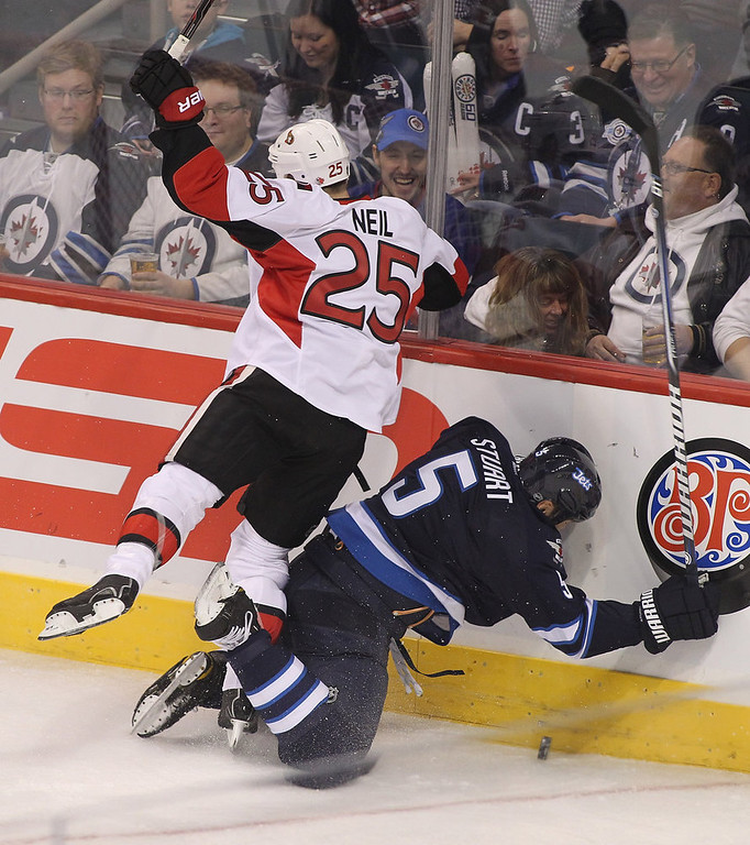Description of . WINNIPEG, MB - JANUARY 19:  Chris Neil #25 of the Ottawa Senators smashes Mark Stuart #5 of the Winnipeg Jets into the boards during first period action on January 19, 2013 at the MTS Centre in Winnipeg, Manitoba, Canada. (Photo by Marianne Helm/Getty Images)