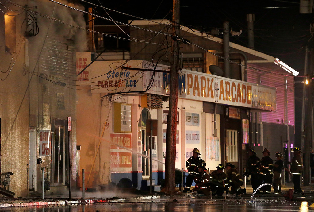 Description of . Firefighters battle a blaze in a building on the Seaside Park boardwalk on Thursday, Sept. 12, 2013, in Seaside Park, N.J. The fire began in a frozen custard stand on the Seaside Park section of the boardwalk and quickly spread north into neighboring Seaside Heights. (AP Photo/Julio Cortez)