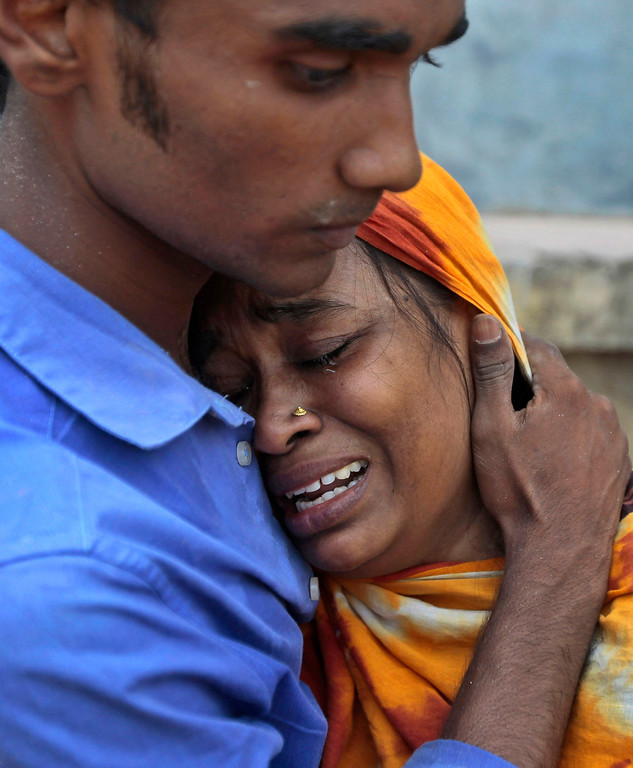Description of . Relatives mourn a victim at the site where an eight-story building housing several garment factories collapsed in Savar, near Dhaka, Bangladesh, Wednesday, April 24, 2013.  (AP Photo/ A.M. Ahad)