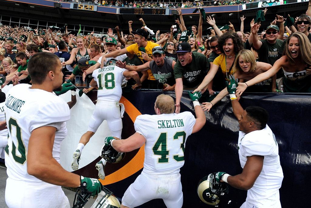 Description of . Colorado State University Rams fans and players celebrate after they defeated Colorado University 22-17 to win the Rocky Mountain Showdown at Sports Authority Field at Mile High Stadium. The Denver Post/ Andy Cross